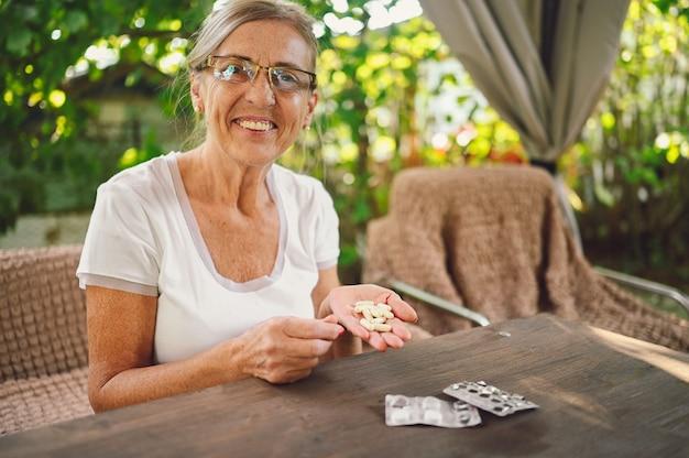 Personnes âgées heureux senior vieille femme en lunettes de prescription prend des médicaments médicaments vitamines pilules à l'extérieur dans le jardin. concept de mode de vie des personnes âgées de soins de santé