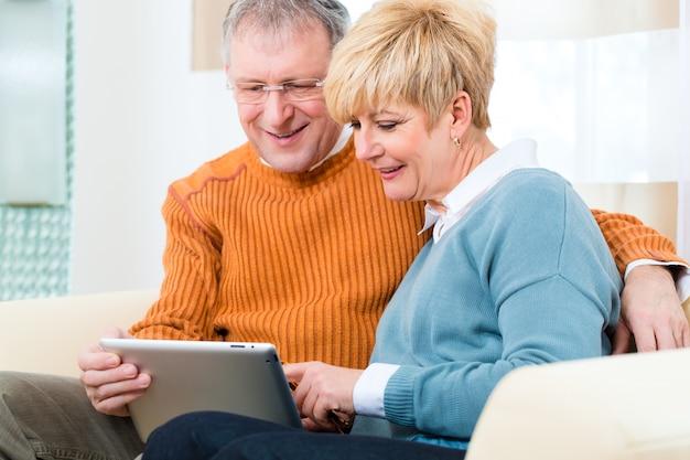 Personnes âgées à la maison avec une tablette