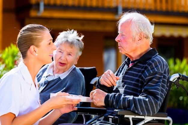 Personnes âgées mangeant des bonbons dans le jardin d'une maison de retraite