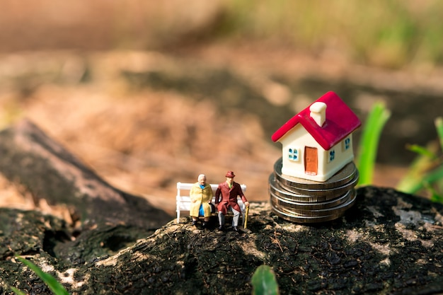 Personnes âgées miniatures assis avec mini maison sur des pièces de pile en utilisant comme concept de retraite professionnelle et de famille
