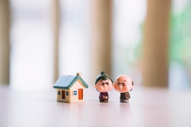Personnes âgées miniatures près d'une maison