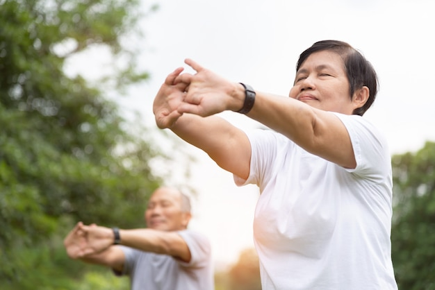Personnes âgées qui s'étirent les mains, les bras avant de faire de l'exercice au parc. heureux couple de personnes âgées asiatiques bénéficiant d'une séance d'entraînement en plein air le matin.