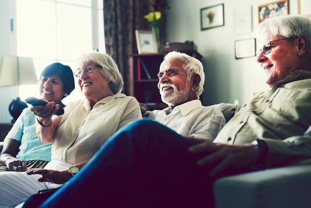 Personnes âgées regardant la télévision dans le salon