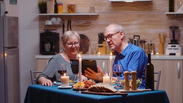 Personnes âgées, retraitées, couple ayant un appel vidéo sur tablette lors d'un dîner romantique. des personnes âgées assises à table, parlant, utilisant la technologie, internet, célébrant leur anniversaire dans la salle à manger.
