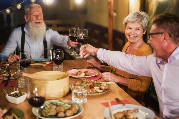 Personnes âgées s'amusant à applaudir avec du vin au dîner sur la terrasse - focus sur le visage féminin