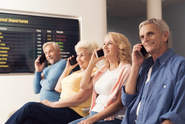Des personnes âgées sont assises dans la salle d'attente de l'aéroport