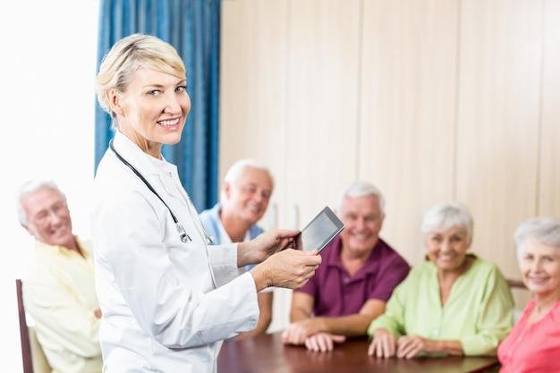 Personnes âgées souriantes et infirmière tenant une tablette
