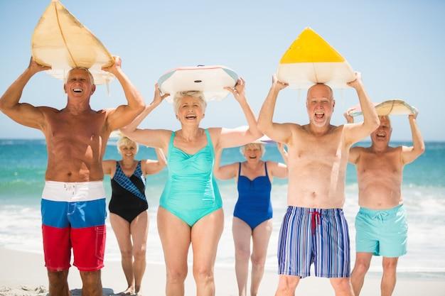 Personnes âgées tenant des planches de surf à la plage