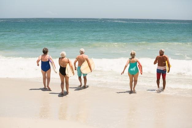 Les personnes âgées transportant des planches de surf à la plage