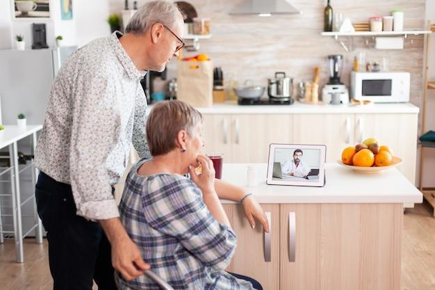 Personnes âgées utilisant une application médicale sur tablette pour parler avec le médecin de sa prescription de pilules consultation de santé en ligne pour les personnes âgées, conseils sur les symptômes de la maladie, webcam de télémédecine du médecin.