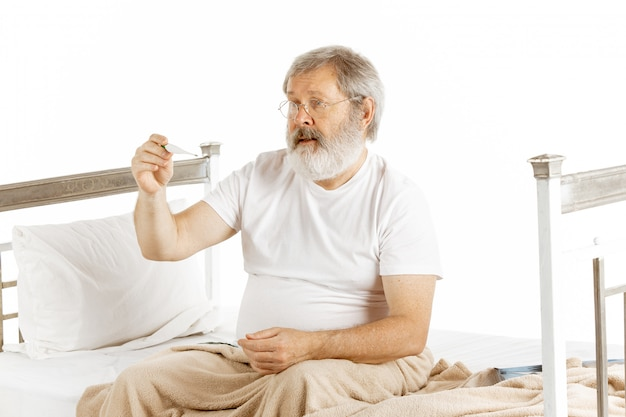 Personnes âgées vieil homme en convalescence dans un lit d'hôpital isolé sur blanc