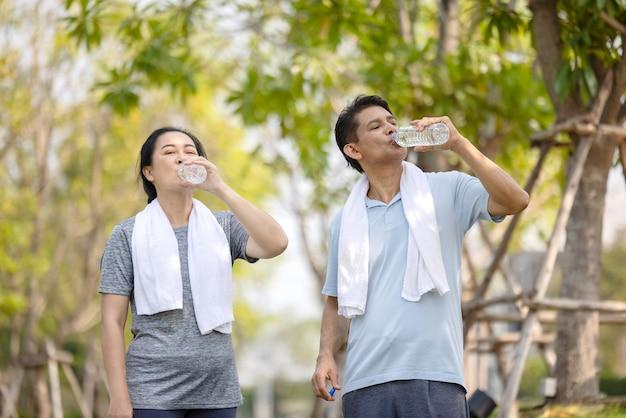 Personnes âgées, vieil homme et femme buvant de l'eau après avoir fait de l'exercice dans le parc