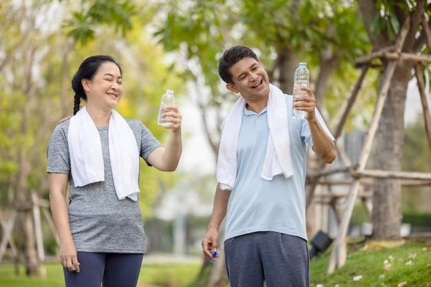Personnes âgées, vieil homme et femme parlant et buvant de l'eau après avoir fait de l'exercice dans un parc