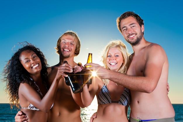 Personnes ayant une fête à la plage avec des boissons