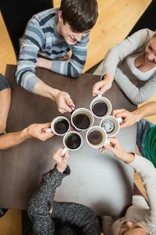 Personnes brandissant des tasses de café