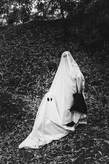 Personnes en costumes de fantômes posant dans le parc
