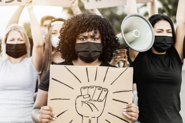 Des personnes de cultures et de races différentes protestent dans la rue pour l'égalité des droits