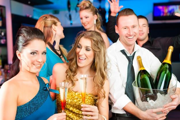 Personnes dans un club ou un bar buvant du champagne