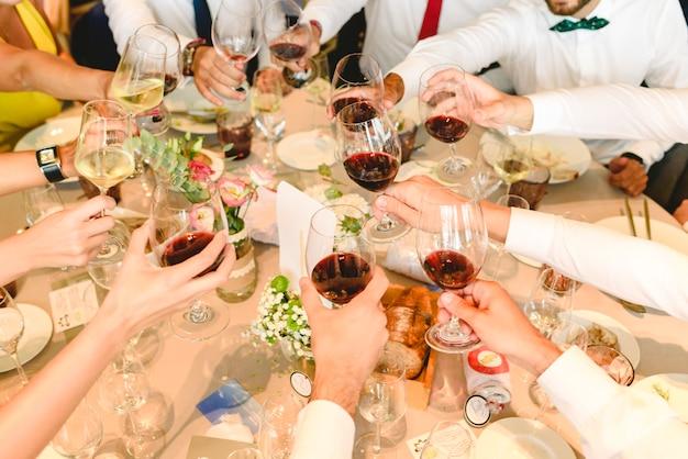 Des personnes dans un cocktail buvant de l'alcool dans leurs verres et s'amusant à la fête.