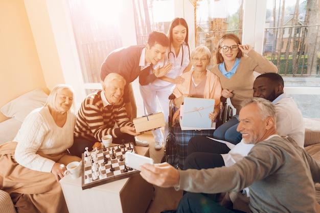 Des personnes dans une maison de retraite font un selfie avec une femme âgée