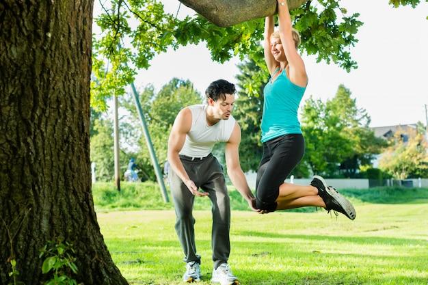 Personnes dans le parc de la ville faisant des mentons ou des tractions sur l'arbre