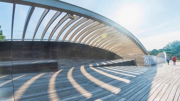 Personnes dans la passerelle de pont en bois avec l'ombre de la structure en acier de la lumière du soleil sur le champ vert arbre forestier avec la ville moderne urbaine et nuage blanc bleu ciel