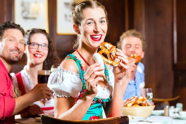 Personnes dans le tracht bavarois mangeant au restaurant ou au pub