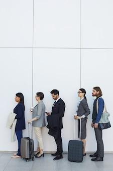 Personnes debout en ligne lors de l'enregistrement à l'aéroport