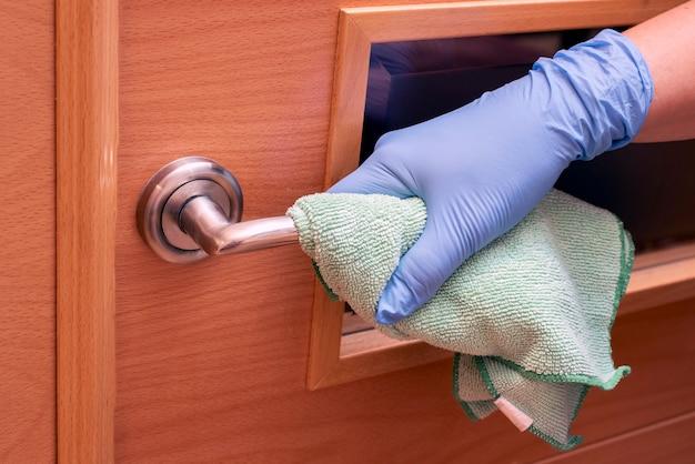 Personnes désinfectant les poignées de porte