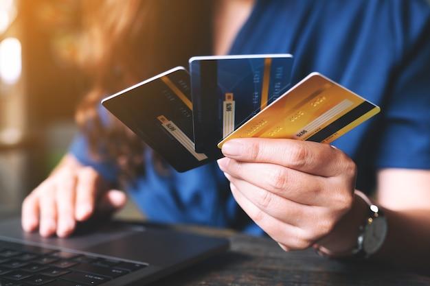 Personnes détenant des cartes de crédit tout en utilisant un ordinateur portable