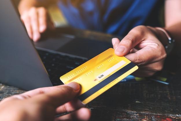 Personnes détenant et donnant une carte de crédit à quelqu'un tout en utilisant un ordinateur portable