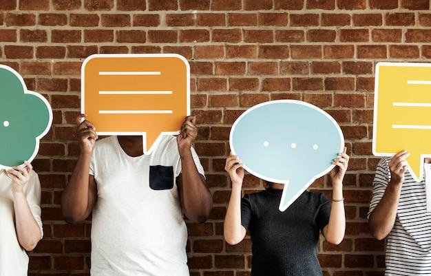 Personnes détenant des icônes de bulle de dialogue