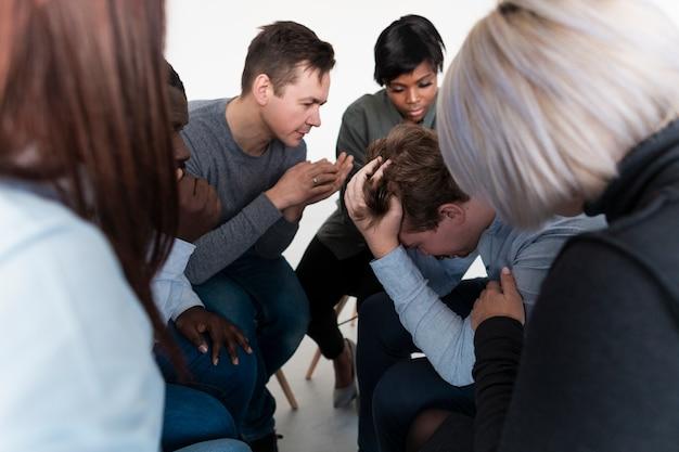 Personnes discutant avec un patient de réadaptation triste