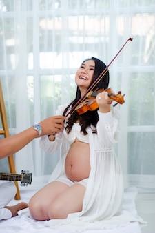 Les personnes enceintes s'entraînent à jouer, jouant à violeta avec bonheur. concept de bonheur