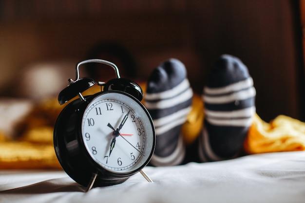 Personnes endormies avec horloge à la main montrant 7 heures avec pied en chaussette sous couverture