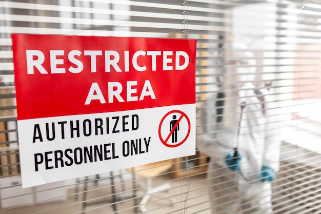 Personnes en équipement de protection désinfectant une zone dangereuse