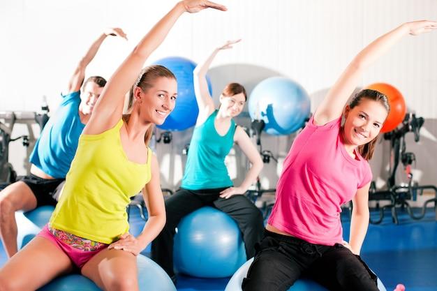 Personnes en gymnase sur ballon d'exercice