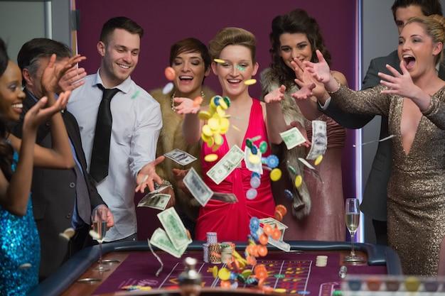 Personnes jetant des jetons et de l'argent sur la table de roulette