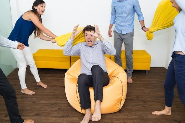 Personnes joyeuses battant leur ami avec des oreillers
