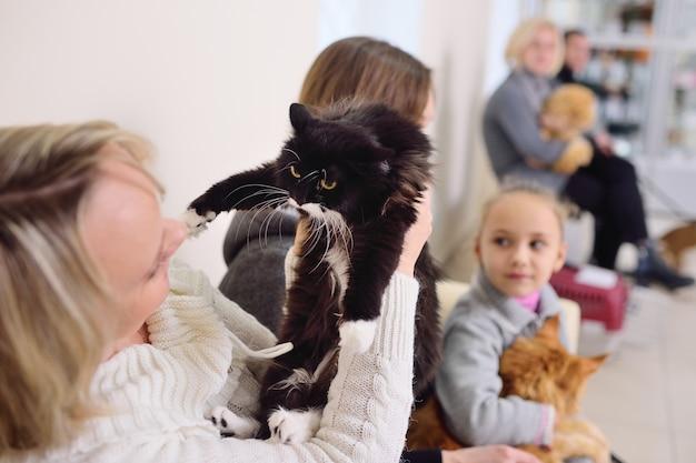 Les personnes avec leurs animaux de compagnie attendent un examen médical à la clinique vétérinaire. la santé des animaux