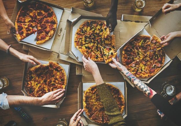 Personnes mains saisissant tranche de pizza