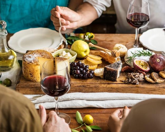 Personnes mangeant un plateau de fromage avec des fruits et du vin de saison
