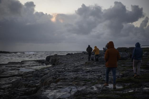 Personnes marchant sur un paysage marin sombre avec des rochers et des nuages