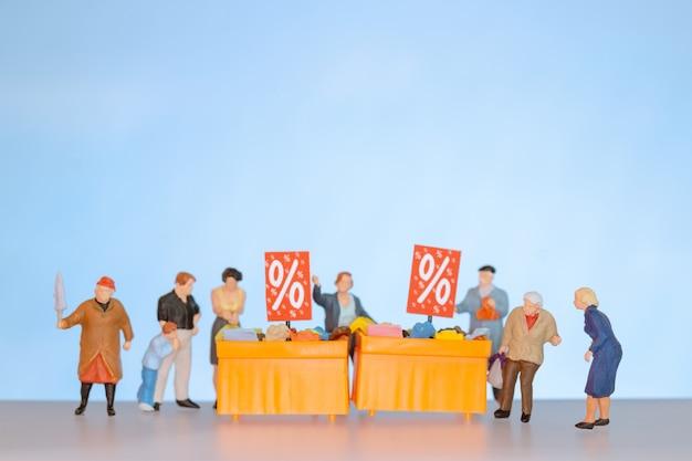 Personnes miniatures, acheteurs avec plateau de réduction pour acheter des articles à prix réduit