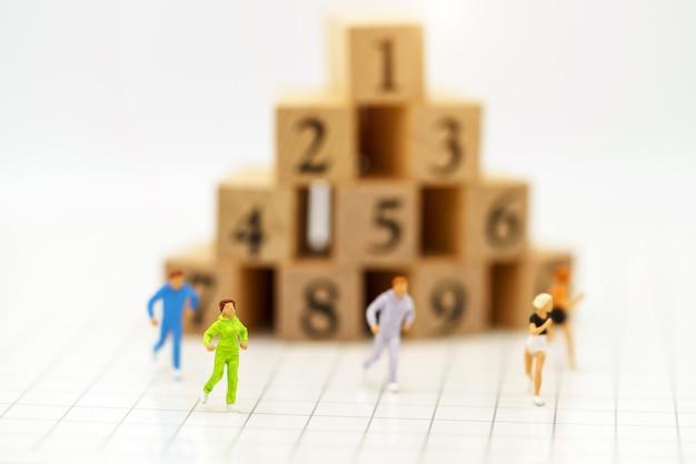 Personnes miniatures en cours d'exécution devant le numéro de la boîte en bois.
