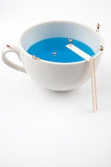 Personnes miniatures dans la piscine tasse tasse