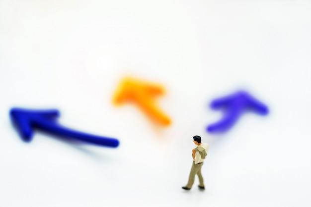 Personnes miniatures debout avec choix de chemin de flèche.