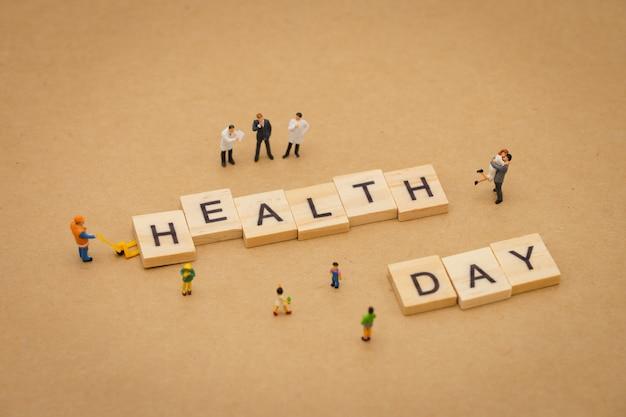 Personnes miniatures debout avec le mot bois journée de la santé utilisant comme arrière-plan journée universelle
