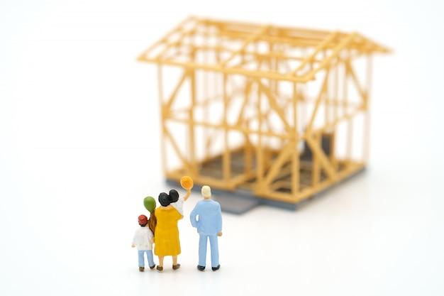 Personnes miniatures debout vérifiez la qualité de la maison.