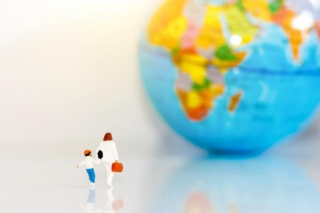Des personnes miniatures, des enfants avec leur mère et leur globe terrestre marchant vers leur destination